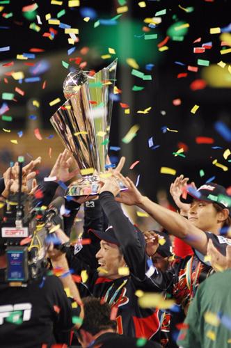 Japan's Seiichi Uchikawa and Akinori Iwamura celebrate with Hiroyuki Nakajima after scoring on Ichiro's single in the tenth inning of the World Baseball Classic Championship game at Dodger Stadium Monday evening. Right, Ichiro holds up the WBC trophy that Japan defended, beating Korea 5-3.