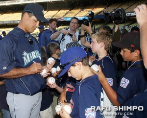 Seattle Mariners manager Don Wakamatsu signs baseballs for Little Leaguers at Dodgers Stadium during the first of the three-game series.