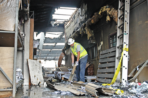 Workers sift through debris on Wednesday at CiX Design in Little Tokyo after a fire destroyed the building on Tuesday evening.  Photo by Mikey Hirano Culross/Rafu Shimpo