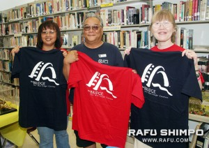 Terri Kuwanoe, left, Glenn Shimizu, and Debbie Mochidome hold t-shirts promoting the Bridge: JCI Heritage Center, a library at the JCI.