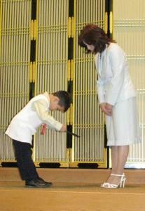 ホール圓子学園長(右)から卒業証書を受け取る卒業生