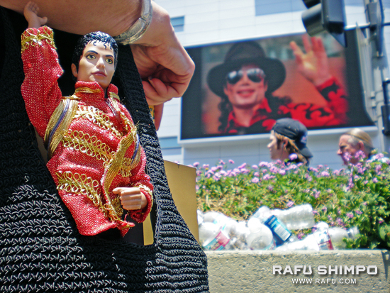 A fan carries a Michael Jackson doll in front of Staples Center, site of a memorial to the pop singer on Tuesday. (Photos by MIKEY HIRANO CULROSS/Rafu Shimpo)