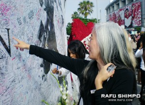 Karen Kimura Joo of Torrance points to where she signed a Jackson tribute wall in front of Staples.