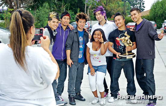 From left, members of America's Best Dance Crew Season 3 winners Quest Crew, D-Trix, Victor Kim, Steve Terada, Ryan Feng, Hok and Brian Hirano pose with a fan in front of Quest Studios in Artesia. (Photos by MICHAEL HIRANO CULROSS/Rafu Shimpo)