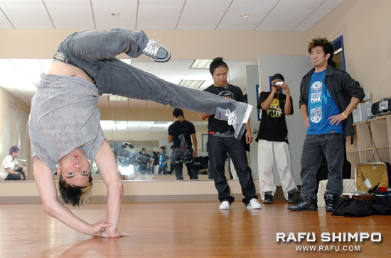 D-Trix shows off his tricking ability while Hok and Steve Terada look on.