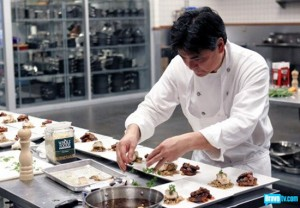 "Roy Yamaguchi puts the finishing touches on his dish on Bravo's ""Top Chef Master."" (Courtesy of Bravo TV)"