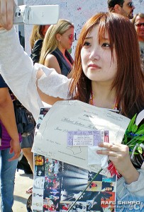 Clutching her ticket and an armful of Jackson memorabilia, Akiko Senoo of Japan tearfully takes photos outside Staples Center.