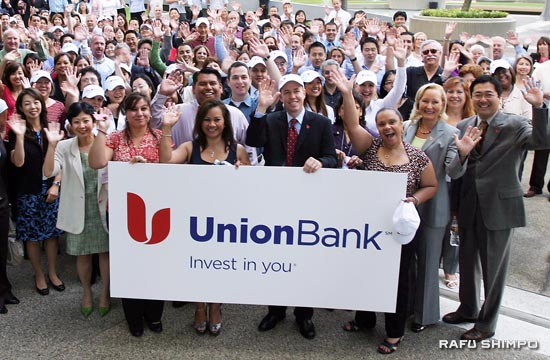 Employees of Union Bank wave on Monday at the official unveiling of the bank's new logo in Los Angeles. (Photos by Jun Nagata)