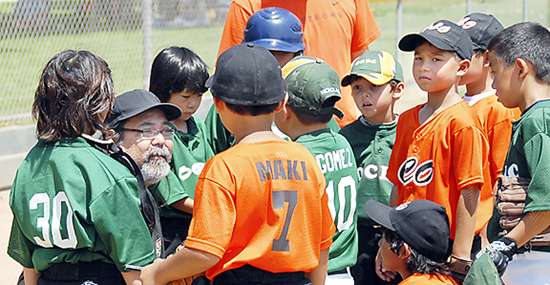 Coach Randy Amuro with the PWM SEYO All Stars imparts some baseball knowledge to his players.