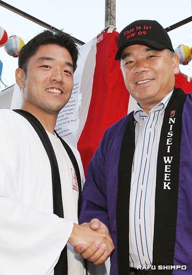 来年度の実行委員長の田村勇人さん(左)と握手を交わすハラ実行委員長