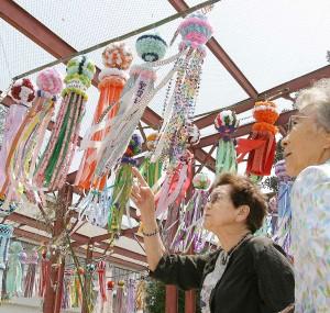 風になびく約250個の七夕飾りを見るトーレンスから来たビバリー・イバさん(左)とドーシー・オオツボさん