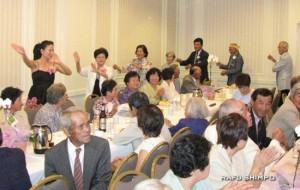 鹿児島おはら節を会場全員で合唱。踊りを披露する山元会長ら