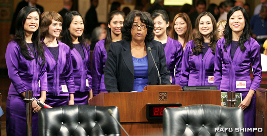Councilmember Jan Perry introduces the Nisei Week Court during a meeting of the Los Angeles City Council on Friday. The Nisei Week Court are from left, Jennifer Akamine, Dana Heatherton, Michelle Hirose, Whitney Itano, Aimee Machida, Nicole Masuda, and Marisa Tamaru. (Photos by MARIO G. REYES/Rafu Shimpo)