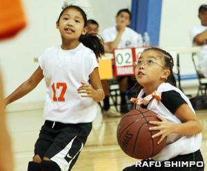 A young girl has her sights set on the basket.