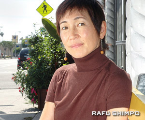 "Emmy nominee Izumi Tanaka reclines in front of a restaurant on Santa Monica Blvd. ""I know the power of media, and I would like to utilize it in a way that gives a positive impact to our world,"" said the filmmaker. (Mikey Hirano Culross/Rafu Shimpo)"