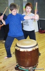A visitor gets a crash course in taiko playing from Yumeko Suzuki, an instructor at Taiko-Lab in Asakusa.