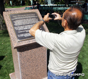 Taking a photo of the plaque which commemorates the time the racetrack was an Assembly Center.