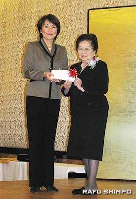 坪井会長から助成金を授与されたJSPACCの馬上真理子代表(左)
