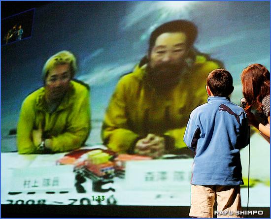 通信衛星使った南極とロサンゼルスの交信。スクリーン上の村上(左)、森澤の両隊員は梅津怜君(右後姿)の質問に優しく答えた