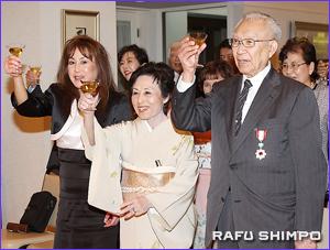 勲章の授章に祝杯を挙げる、右から山口氏、妻淑子さんと娘のジューンさん