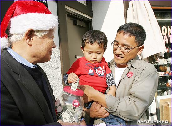 お父さんに抱っこされ募金箱にお札を入れるタイゾウくん(中央)。左のサンタは南加日商の加藤譲孜理事