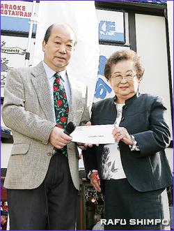 敬老の大石さん(左)に寄付金1000ドルを手渡す坪井・南加日系婦人会会長