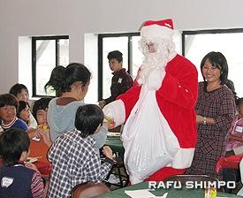 サンタクロースからプレゼントをもらう子どもたち