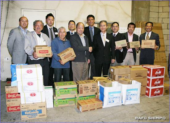 敬老に多くの日本食を寄付した七味会のメンバーら。中央で握手する2人が清水会長(右)と敬老引退者ホームの大石剛施設長