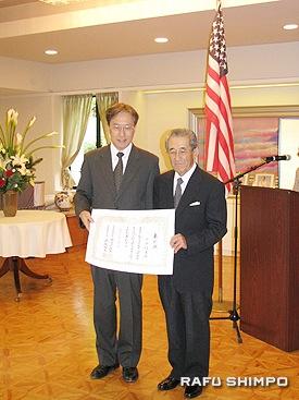 伊原総領事から賞状を手渡される小山氏(右)