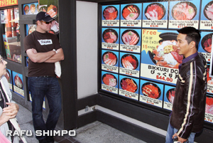Tour guide Brian Takahashi, right, explains the colorful pictures that adorn the outside walls of Wakasaya, one of the main stops on the Gastronaut Tour.
