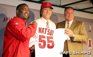 Matsui holds up his new Angels jersey with Angels G.M. Tony Reagins, left and Angels manager Mike Scioscia, right.
