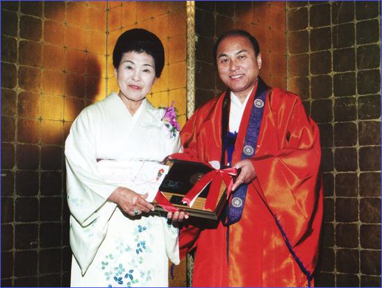 池坊ロサンゼルス支部創立40周年記念祝賀式典で専永宗匠(右)から記念の盾を贈られる新橋和子さん=1997年