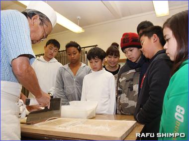 そばを同じ太さで切る塩川さん(左)。ウエストコビナの日本語学校でのそば打ちの実演