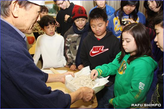 塩川さんが打ったそばを子どもたちに披露する佐藤さん(左)