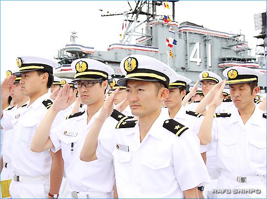 国歌斉唱で敬礼する実習幹部ら。巨艦ミッドウェイの規模の大きさに驚いていた