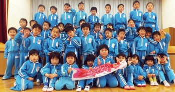 Children from Shiritsu Kahoku Kindergarten in Ishinomaki, Miyagi Prefecture, pose with a koinobori flag inscribed with inspirational messages from Washington State University students.