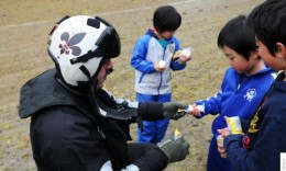 A U.S. naval air crewman hands treats to Japanese children during a humanitarian assistance mission in Oshima on March 21, 2011. (U.S. Navy)
