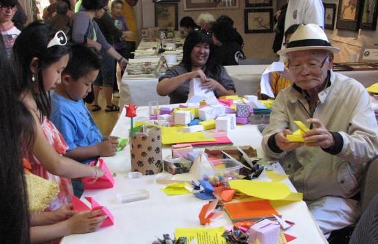 Familia japonesa haciendo origami: un niño, una niña y un abuelito