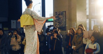 Visitors clamor to photograph a model in the kimono fashion show.