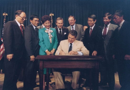 President Ronald Reagan signs the redress bill into law on Aug. 10, 1988. The Japanese American members of Congress were among those in attendance. (Ronald Reagan Library)