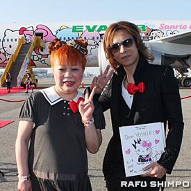 キティー3代目デザイナーの山口裕子取締役キャラクター制作部長(左)が自ら描いたヨシキティーの色紙を手にポーズをとるヨシキさん