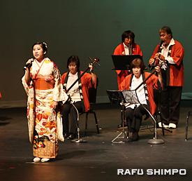 竹嶺会の演奏とともに「シャンシャン馬道中唄」を披露する奨学金受賞者の水島茜さん(左端)
