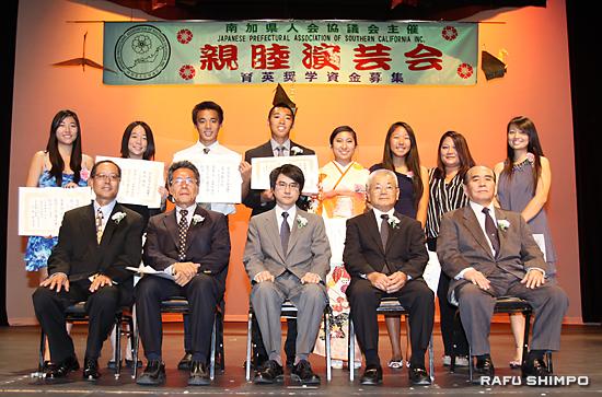 日本文化を継承する若い8人の受賞者(後列)に贈られた奨学金の授与式。前列中央から新村領事、岩下会長、野崎住吉・育英奨学資金部部長