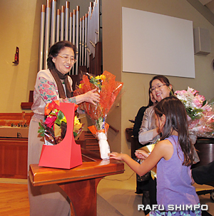 歌い終え、参加者から花束を贈られる北野さん(左)