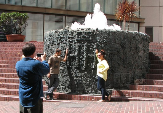 Tourists pose for a photo in front of Ruth Asawa's iconic fountain in Union Square.