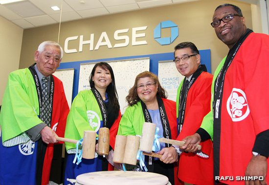 From left, Yoshitaka Ena, Stephanie Nakata, LizAnn Shimamoto, Terry Hara and Antonio Manning perform the **kagami biraki,** breaking of the sake barrel, at the opening of Chase Bank in Little Tokyo last Friday. (MARIO G. REYES/Rafu Shimpo)