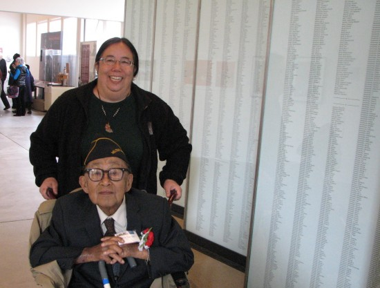 MIS veteran and noted artist Lewis Suzuki and his daughter Fumi next to the honor roll of MIS soldiers.