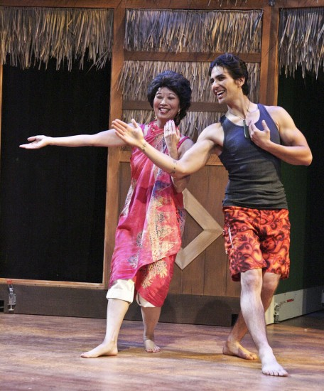 "Jeanne Sakata as Tomi gets a hula lesson from Kimo, played by Tui Asau, in East West Players' ""The Nisei Widows Club: How Tomi Got Her Groove Back."" (Photo by Michael Lamont)"