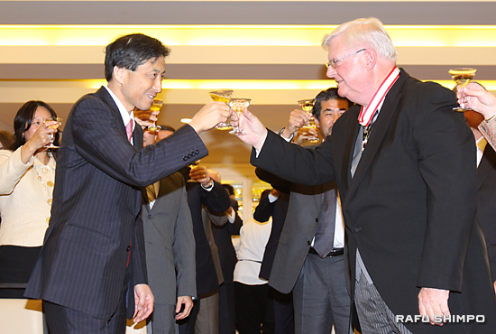 叙勲を祝い新美総領事(左)と乾杯するデッカー氏