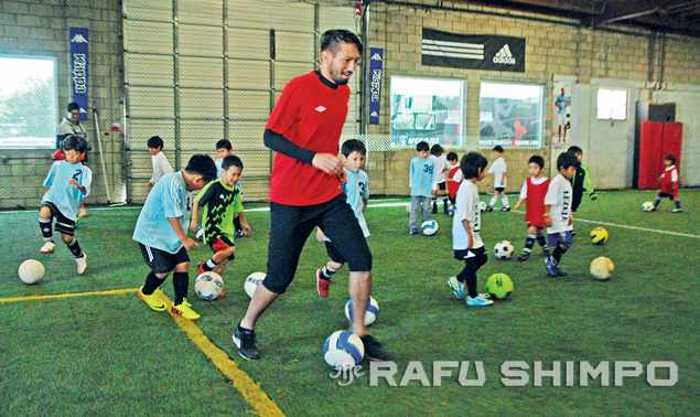 Jun Marques Davidson, a midfielder for the MLS Vancouver Whitecaps FC, runs the young players through some warm-up drills at the Dec. 15 futsal clinic organized by the Lezele Football Club. (Photos by Mikey Hirano Culross/Rafu Shimpo)